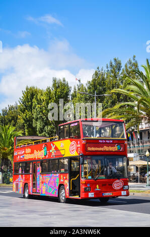 Funchal, Madeira, Portugal - Sep 10, 2019: Red double-decker sightseeing bus driving with tourists on the road in Madeiran capital city. Hop on hop off buses, transport service. Tourist attraction. - Stock Photo