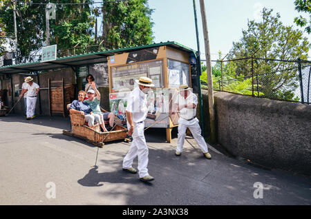 Monte, Madeira, Portugal - Sep 14, 2019: Wicker Basket Sledges drivers, Carreiros do Monte, driving tourists downhill. Traditional mean of transport, now a tourist attraction. Typical straw hats. - Stock Photo