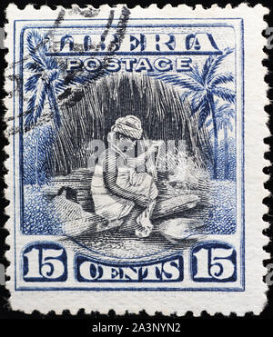 Woman working on old postage stamp of Liberia - Stock Photo