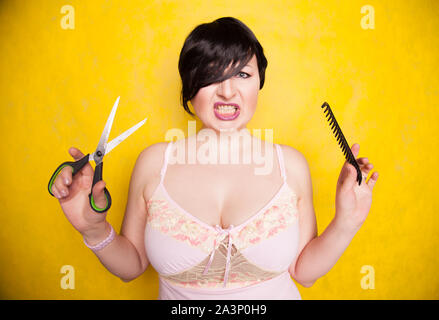 charming emotional plus size woman cuts her hair with scissors because she wants a short haircut on a yellow background in the Studio.