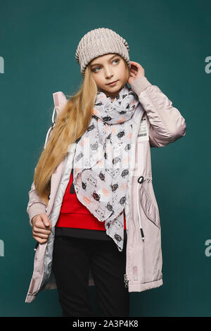Happy girl wearing in jeans, boots, a warm jacket and hat. Cropped portrait of a teenage blonde model girl in modish winter's clothes posing over the - Stock Photo
