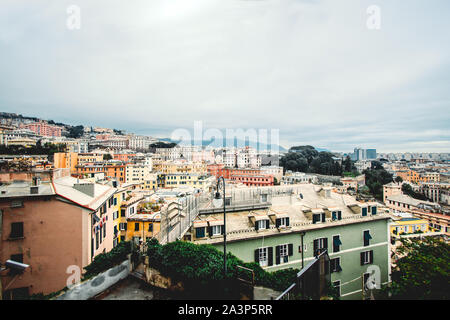 Many beautiful old italian houses painted in bright colors with mountains on the background.An amazing cityscape of some public housing in Genova