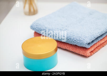 Towels on white table in bath room background. - Stock Photo