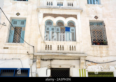 The exterior facade of an old traditional house (with windows, shutters and bars) in the Medina (old city) of Tunis, Tunisia. - Stock Photo