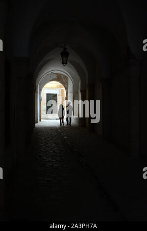 A young Tunisian couple walking through a covered pedestrian alleyway in streets of the Hafsia quarter of the Medina (old city) of Tunis, Tunisia. - Stock Photo