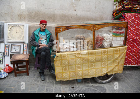 An elderly food merchant selling sweets, halwa and pastries sitting at his stall in the market of the kasbah, in the Medina of Tunis, Tunisia. - Stock Photo