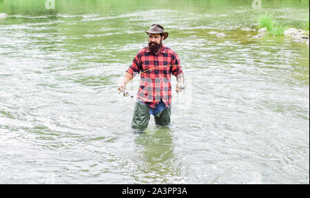 Man bearded fisher. Fishing requires to be mindful and fully present in moment. Fisher fishing equipment. Rest and recreation. Fisher masculine hobby. Fish on hook. Brutal man stand in river water. - Stock Photo