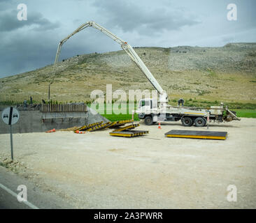 Pouring concrete through the top using a crane machine - Stock Photo