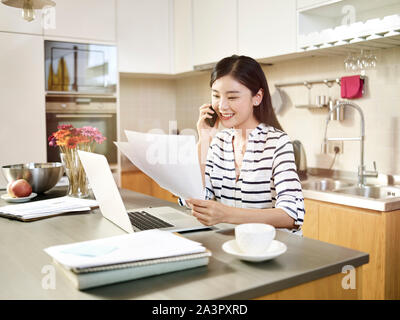 young asian woman sitting at kitchen counter working using laptop computer talking on cellphone. - Stock Photo