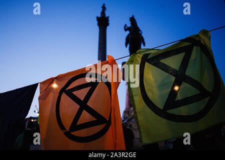 Sheets of cloth bearing the logo of climate change activist group Extinction Rebellion (XR) hang from a clothes line in Trafalgar Square as darkness falls on the second day of the group's 'International Rebellion' in London.By early Tuesday evening the Metropolitan Police were reporting that a total of 531 arrests had been made over the two days of protests in the city so far, with police officers working to clear people and tents from many of the sites taken over by activists yesterday. Similar blockades by Extinction Rebellion in April, at sites including Oxford Circus and Waterloo Bridge, s - Stock Photo