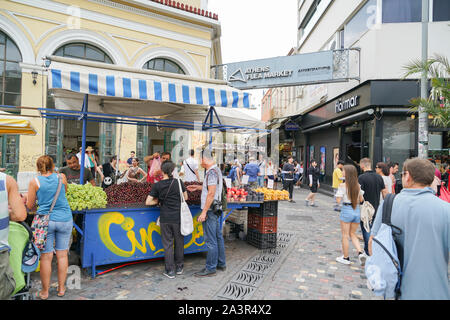 Athens Greece - July 15 2019; Tourists pass by and buying fruit from street fruit vendor under Athens Flea Market sign in Plaka. - Stock Photo