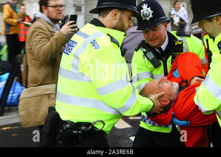 Police taking great care to protect the head of an Extinction Rebellion protestor during the execution of the arrest on the 8th October 2019. Extinction Rebellion shut down streets of London. Central London closed down by demo. - Stock Photo