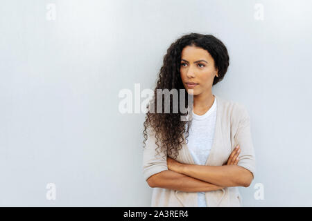 Staring young woman staring intently to the side with folded arms and an intense expression against a white exterior wall with copy space - Stock Photo