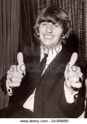 Ringo Starr,  Drummer of The Beatles, giving a 'thumbs up' sign before leaving Heathrow Airport. 1964, London, England, UK - Stock Photo