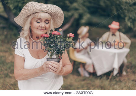 Portrait of a beautiful grandmother in the garden who is smelling a rose flower. Happy family in the background. Grandpa razvovarivaet with her grandd - Stock Photo