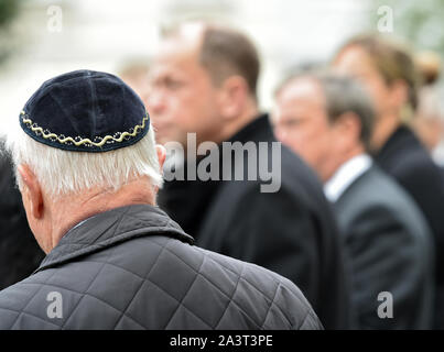 Duesseldorf, Germany. 10th Oct, 2019. A man with kippa watches politicians standing in front of the entrance to the New Synagogue. After the fatal shots in Halle on Thursday, the politicians are sending a signal of solidarity with the Jewish communities in Germany. Credit: dpa picture alliance/Alamy Live News - Stock Photo