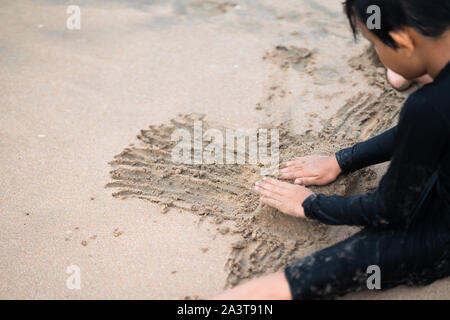 Little Asian boy is playing sand on the beach. Vacation and relax concept. Stock Photo