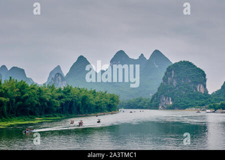 Tourist boats on Li river with carst mountains in the background - Stock Photo