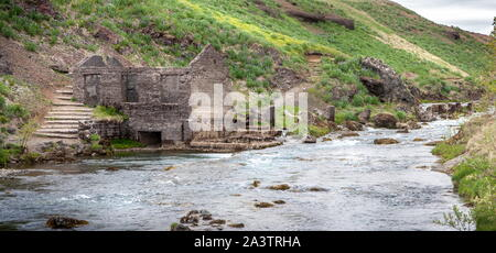 Panorama of the ruins of an old stone mill standing by the river - Stock Photo
