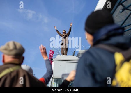 London, UK. 10th Oct, 2018. A protester chants slogans while making gestures during the demonstration at the airport rooftop in London.Extinction Rebellion protesters plan to cause chaos at the London City airport for three days to raise awareness of the climate emergency. Credit: Ryan Ashcroft/SOPA Images/ZUMA Wire/Alamy Live News - Stock Photo