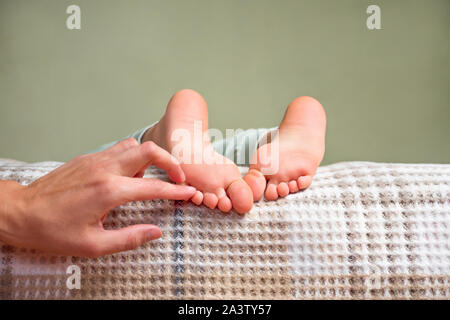 Children's feet. Barefeet on the bed. Kid's feet in bed. Tickling for fun. Kids taking a rest focus on barefeet. Gentle touch of baby's feet. Waking up process. Soft touch Copy space. Part of series - Stock Photo
