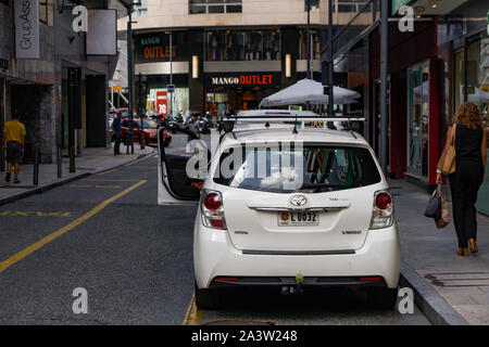 Andorra la Vella, Andorra parked taxi at designated stop. White taxi with Principat D Andorra car license plate at a shopping area in the capital. - Stock Photo