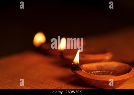 Stock photo of Diwali diya or clay oil lamp lit during the festival of lights in India. Dark moody background image of diyas for Diwali greeting card. - Stock Photo
