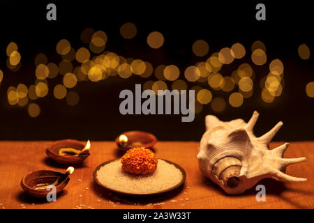 Diwali - an Indian festival known as Festival of Lights. Religious traditional clay diya lit on a wooden surface decorated with flowers, rice grains a - Stock Photo