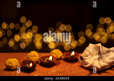 Diwali diya clay lamps decorated with flowers and shankha burning or glowing on a wooden background isolated in black with bokeh lights and copy space - Stock Photo