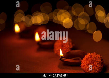 Diwali decoration with traditional diya oil lamps, marigold flowers and golden bokeh during Diwali festive celebration night. - Stock Photo