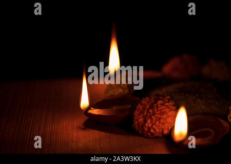 Diya lamps lit during diwali celebration with natural moody lighting and selective focused. Background image concept for religious tradition. - Stock Photo