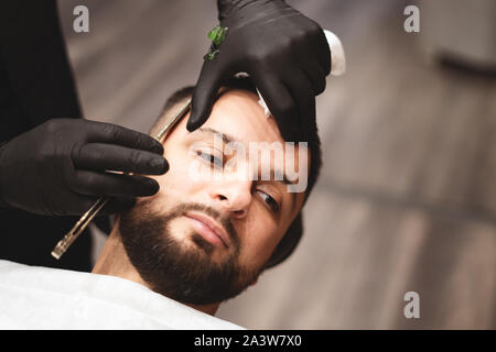 Shaving a beard in a barbershop with a dangerous razor. Barber Shop Beard Care. Drying, cutting, cutting a beard. Selective focus - Stock Photo