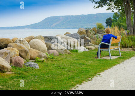 Woman on bench overlocking the 'Blue Mountain of Collingwood from Marian and Water Dam in Thornbury, Ontario, Canada, North America - Stock Photo