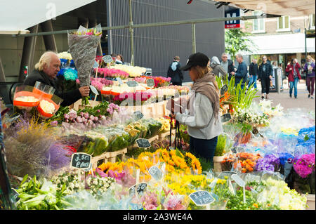 Albert Cuypmarket in Amsterdam, market stall with flowers near entrance of metro station. - Stock Photo