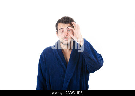 Portrait of sleepy young businessman wears blue bathrobe trying to hold his his eye open feeling tired needs to sleep isolated on white background. - Stock Photo