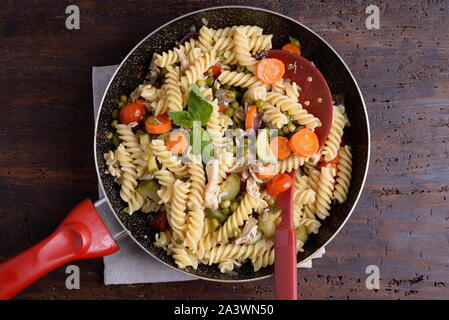 Fusilli in a pan with vegetables and chunks of chicken on the table - Stock Photo