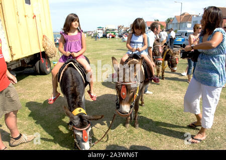 Two girls on Donkeys at a fair - Stock Photo