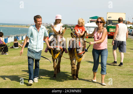 Children on Donkeys at a fair - Stock Photo