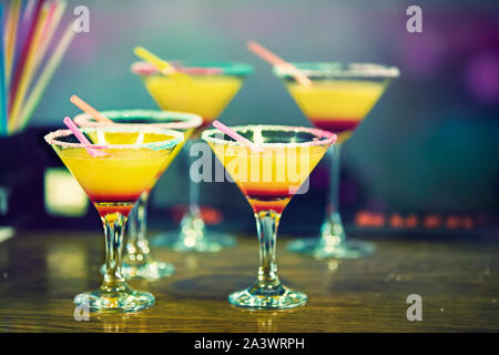 Glasses with a yellow cocktail on the table. Orange drink at the bar counter. - Stock Photo