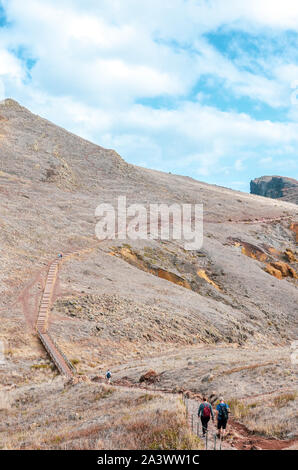 Hikers on a trail leading to the Ponta de Sao Lourenco in Madeira island, Portugal. Easternmost point of Madeira. Volcanic landscape. Hilly, rocky terrain. Portuguese landscapes, active vacation. - Stock Photo