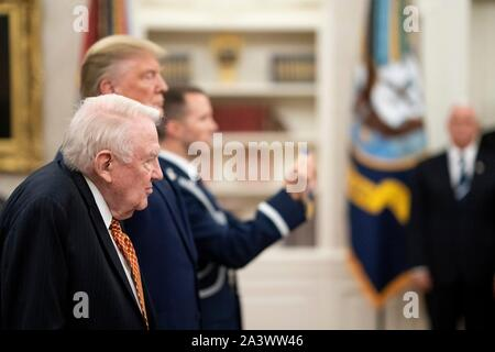 U.S President Donald Trump presents former Attorney General Edwin Meese with the Presidential Medal of Freedom during a ceremony in the Oval Office of the White House October 8, 2019 in Washington, DC. - Stock Photo