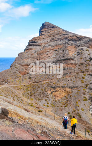 Tourists walking on a hiking path in Ponta de Sao Lourenco, Madeira, Portugal. Peninsula, easternmost point of the Portuguese island. Volcanic landscape, soil. Hilly, rocky terrain. Hikers on a way. - Stock Photo