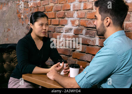 two young people a guy and a girl talking about something serious while sitting at a table in a cafe on the background of a rough brick wall - Stock Photo