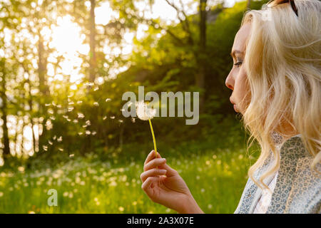 Closeup Of Young Woman Blowing Dandelion Seeds - Stock Photo
