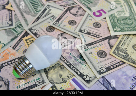 LED bulb in the background of different countries currency notes.   Economy concept - image - Stock Photo