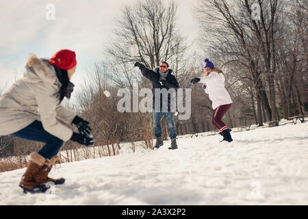 Group of millenial young adult friends throwing snowballs in wintertime in a snow filled park - Stock Photo