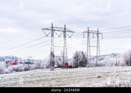 Power grid and tower in a Norwegian village in a winter snowy day in the Skedsmo,  a municipality in Akershus county, Norway. - Stock Photo