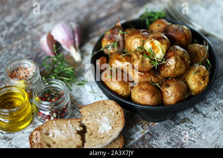 Baked potatoes in a peel in a cast-iron skillet. Rustic potatoes. Selective focus. Macro. - Stock Photo