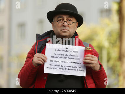 Duesseldorf, Germany. 10th Oct, 2019. A man stands in front of the synagogue and holds a sign with the inscription 'Liebes Deutsches Volk: Es sind die Blau-Braunen, nationalenistischen Rattenfänger, die lie, rush und Morden! We stand by our Jewish fellow citizens and commemorate the victims! The Mehmet'. During attacks in the middle of Halle an der Saale in Saxony-Anhalt two people were shot dead on 09.10.2019. Credit: David Young/dpa/Alamy Live News - Stock Photo