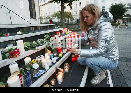 Duesseldorf, Germany. 10th Oct, 2019. Ute Pfeil from Düsseldorf puts flowers on the stairs in front of the synagogue and lights a candle. During attacks in the middle of Halle an der Saale in Saxony-Anhalt two people were shot dead on 09.10.2019. Credit: David Young/dpa/Alamy Live News - Stock Photo